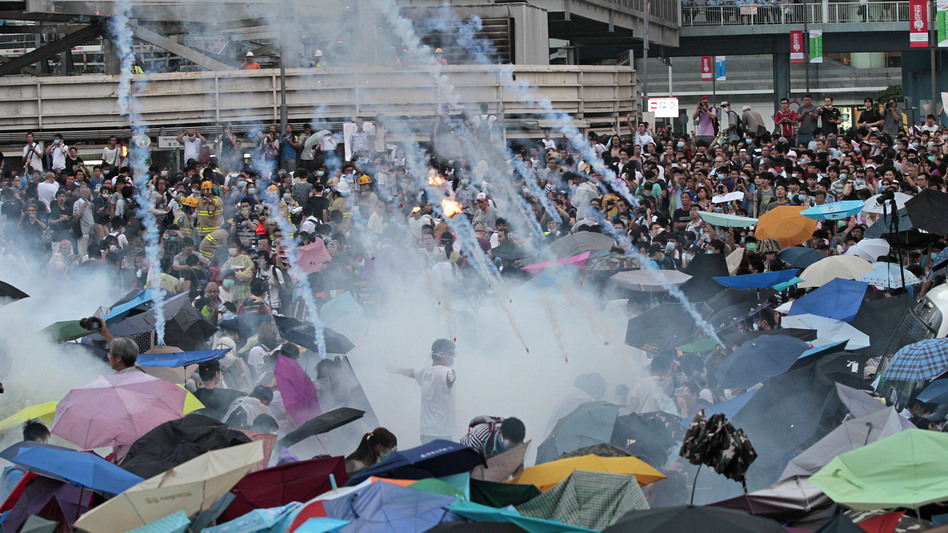 Riot police launch tear gas into a crowd of thousands of protesters outside the government headquarters in Hong Kong Sunday. Police warned of further measures as they tried to clear the streets. Wally Santana/AP