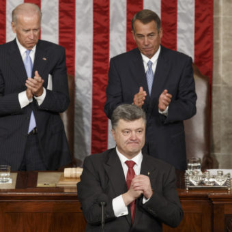 Ukrainian President Petro Poroshenko, joined by Speaker of the House John Boehner and Vice President Joe Biden, acknowledges lawmakers' applause after addressing a joint meeting of Congress. J. Scott Applewhite/AP