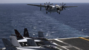 A U.S. military plane lands Aug. 11 on the U.S. Navy aircraft carrier USS George H.W. Bush in the Persian Gulf. U.S. public support of airstrikes against Islamic militants jumped sharply, according to a new poll, as President Obama prepares a strategy. Hasan Jamali/AP