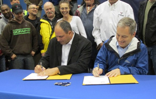 Adam Beck and Gov. Sean Parnell sign the contact for Vigor Alaska to build two new state ferries. (Photo from KRBD.org)
