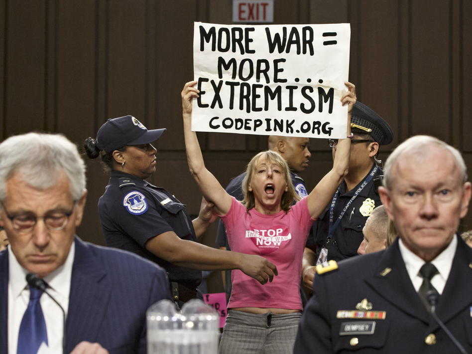 Members of the anti-war activist group CodePink interrupt a Senate Armed Services Committee hearing with Defense Secretary Chuck Hagel (left) and Gen. Martin Dempsey, chairman of the Joint Chiefs of Staff. J. Scott Applewhite/AP