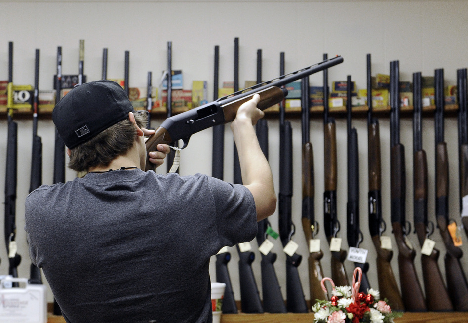 A customer checks out a shotgun at a store in College Station, Texas. Pat Sullivan/AP