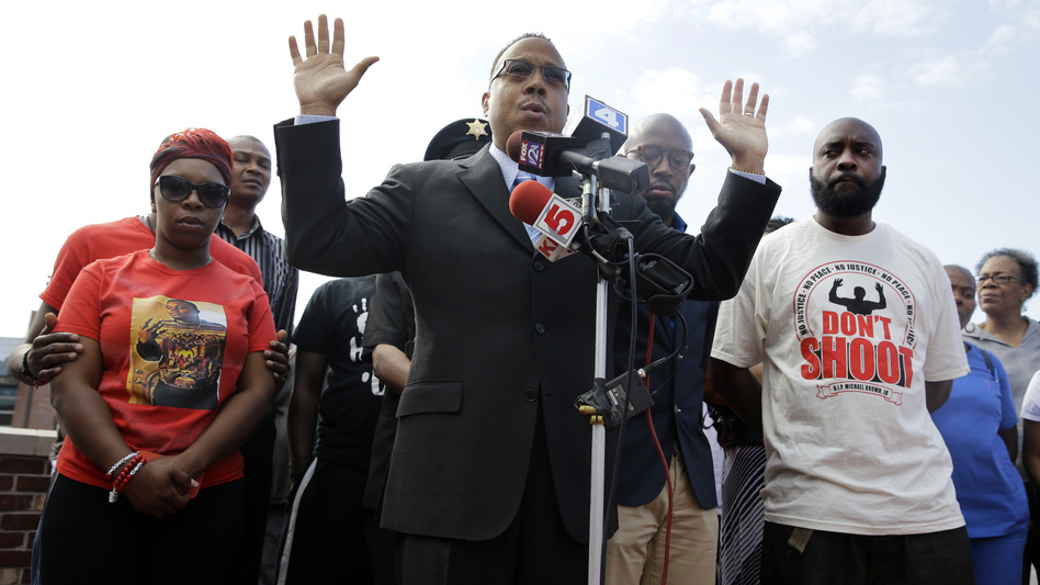 Michael Brown's parents Lesley McSpadden (left) and Michael Brown Sr. (right) flank attorney Anthony Gray as he speaks at a news conference held Tuesday, one month after Michael Brown was shot and killed in Ferguson, Mo. (Photo by Jeff Roberson/AP)