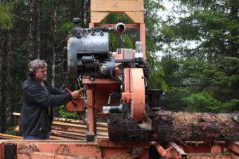 Chris Fry milling a spruce log. (Photo by Elizabeth Jenkins/KFSK)