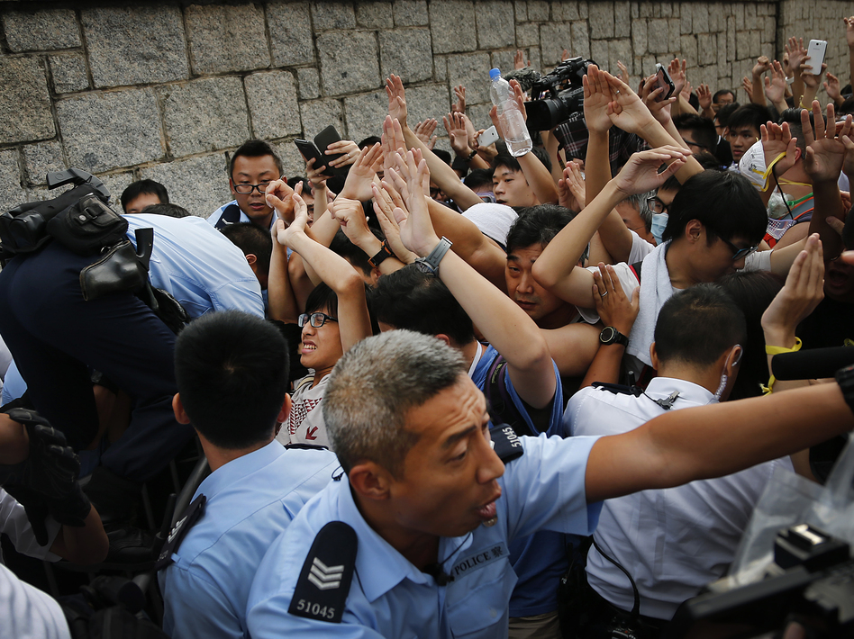 Student protesters in Hong Kong resist during a change of shift for local police but backed down after being reassured they could reoccupy the pavement outside the government compound's gate. Wong Maye-E/AP