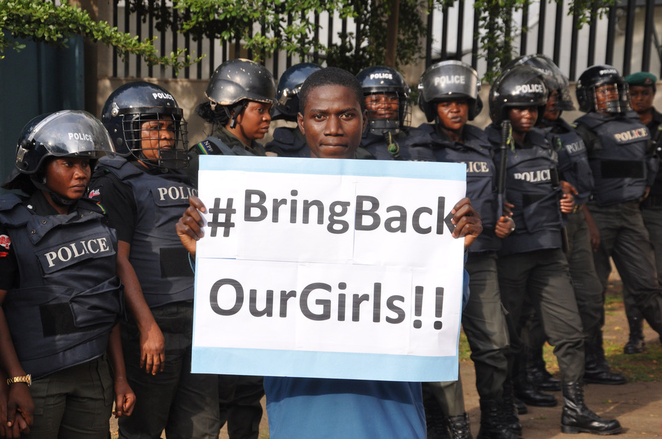 A man poses with a sign in front of police officers in riot gear during a demonstration calling on the government to rescue the kidnapped girls of a government secondary school in Chibok, in Abuja, Nigeria, on Tuesday. Olamikan Gbemiga/AP