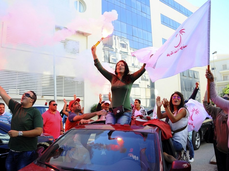 Supporters of the secular Nidda Tounes (Tunisia Calls) party celebrate their victory in parliamentary elections before the elections were official earlier this week in Tunis. Hassene Dridi /AP