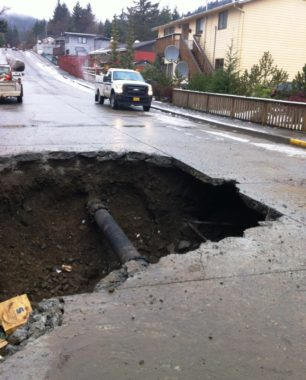 A large hole surrounds a repaired Ketchikan water-main break in December, 2013. The fill dirt under the street was washed away. Water and sewer line repairs are on the city's ballot.