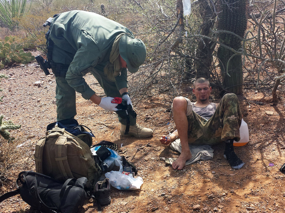 An unidentified U.S. Border Patrol agent, left, helps an immigrant, including setting up intravenous fluid replacement for dehydration, near Sells, Ariz. on June 25. (Astrid Galvan/AP)