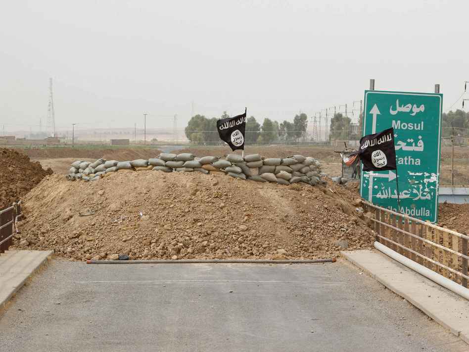 Islamic State flags on the Mullah Abdullah bridge in southern Kirkuk earlier this week. A U.N. report says the extremist group has perpetrated possible war crimes and crimes against humanity. Reuters/Landov