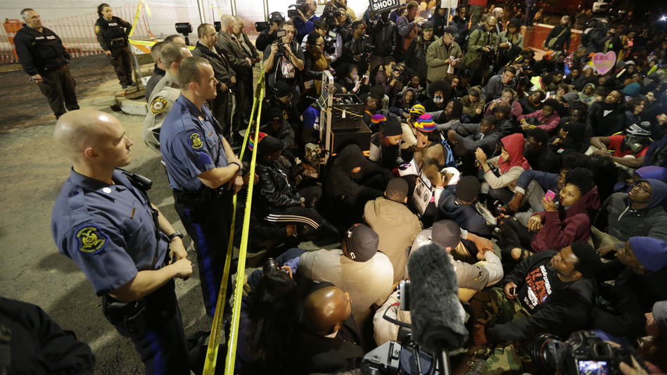 Protesters sit silently for over four minutes at the Ferguson Police Department Saturday, during a rally in remembrance of Michael Brown in Ferguson, Mo. While the demonstration was peaceful, police arrested protesters elsewhere. Charles Rex Arbogast/AP
