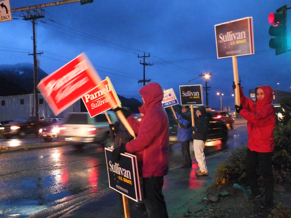 Sign wavers at 10th Street and Egan Drive in Juneau try to get the attention of evening commuters on Election Day. (Photo by Matt Miller/KTOO)