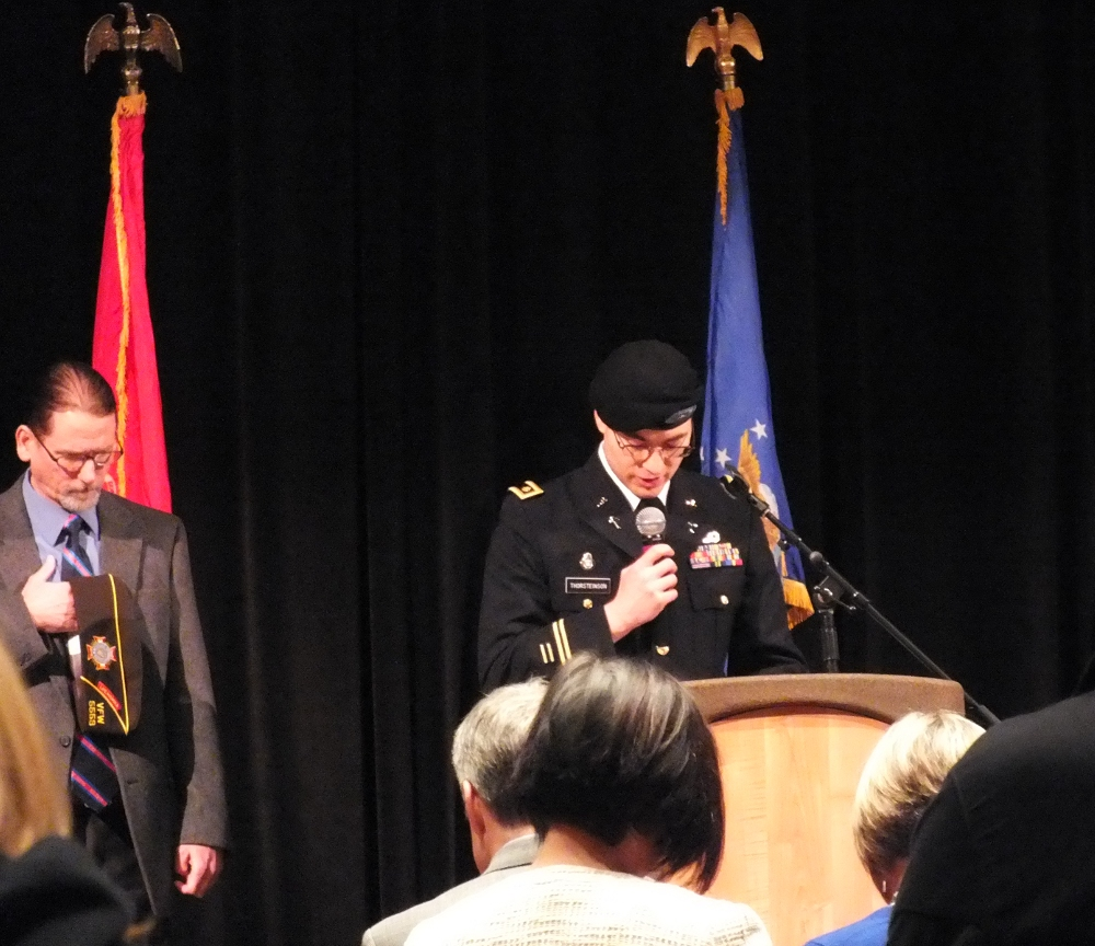 Chaplain Kirk Thorsteinson delivers the invocation as Cmdr. Dan McCrummen of VFW Post 5559 listens during Veterans Day observances at Centennial Hall on Nov. 11, 2014. (Photo by Matt Miller/KTOO)