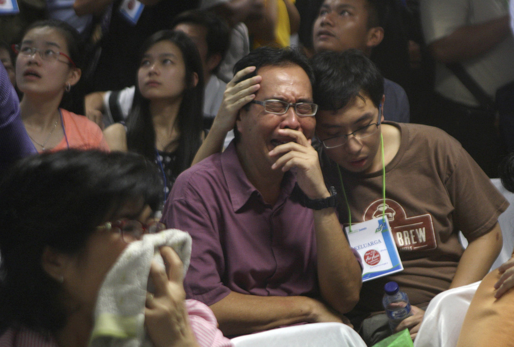 Relatives of passengers of the missing AirAsia Flight 8501 react upon seeing the news on television about the findings of bodies on the waters near the site where the jetliner disappeared in Surabaya, East Java, Indonesia, on Tuesday. Trisnadi/AP