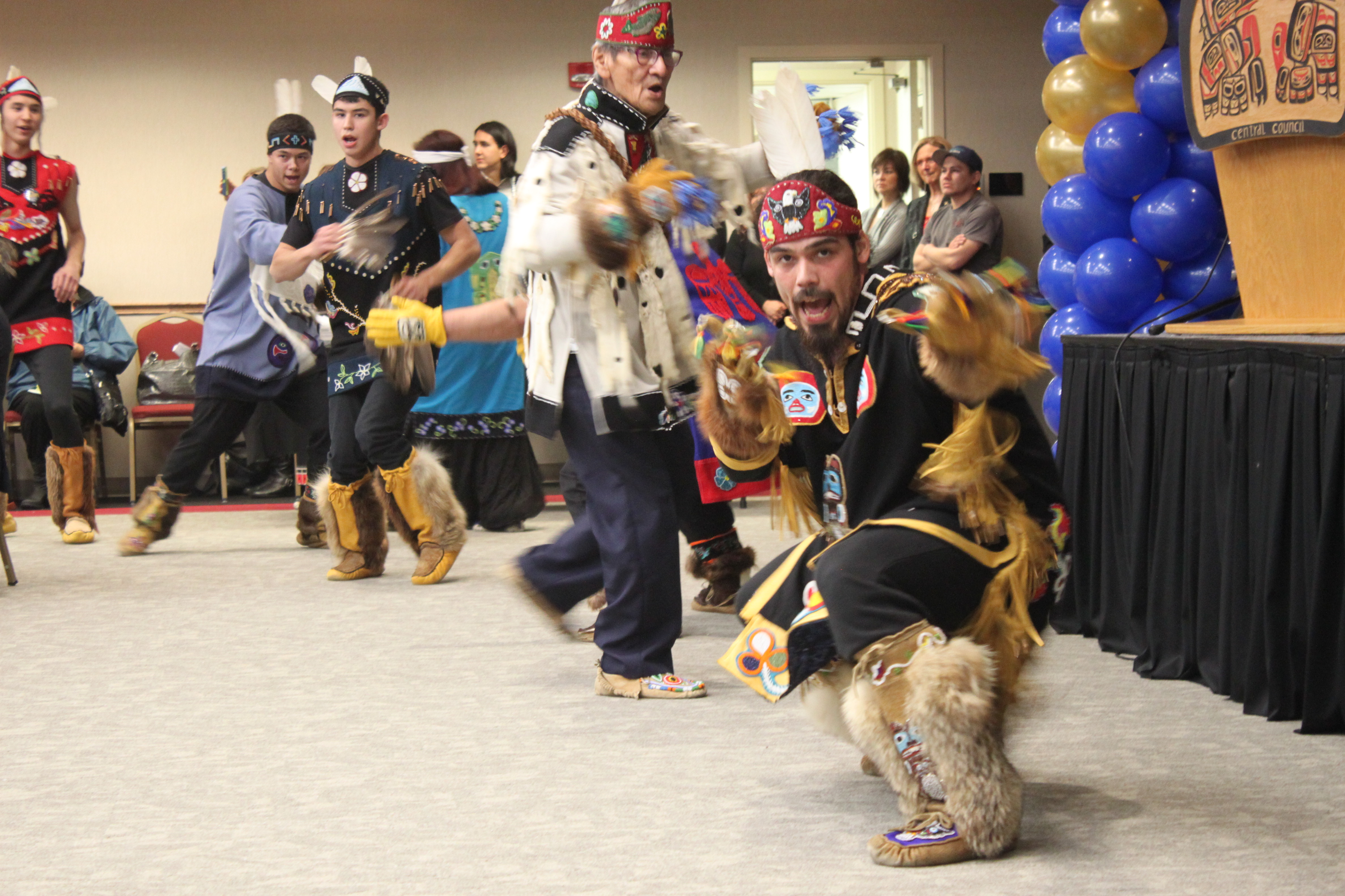 The Mount St. Elias Dancers of Yakutat took the stage during the inauguration and again at the welcome reception. John Patrick Buller leads the dancers in. (Photo by Lisa Phu/KTOO)