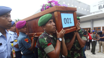 Indonesian soldiers carry a coffin containing a victim of AirAsia Flight 8501 upon arrival at Indonesian Military Air Force base in Surabaya, Indonesia, on Wednesday. Firdia Lisnawati/AP