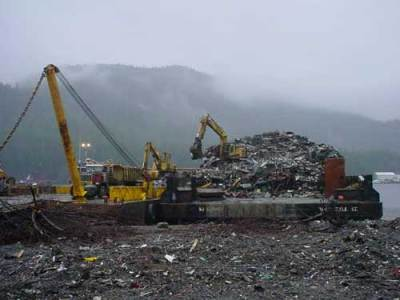Heavy equipment loads scrap metal onto a barge in Ketchikan. (Photo courtesy Ketchikan Gateway Borough)