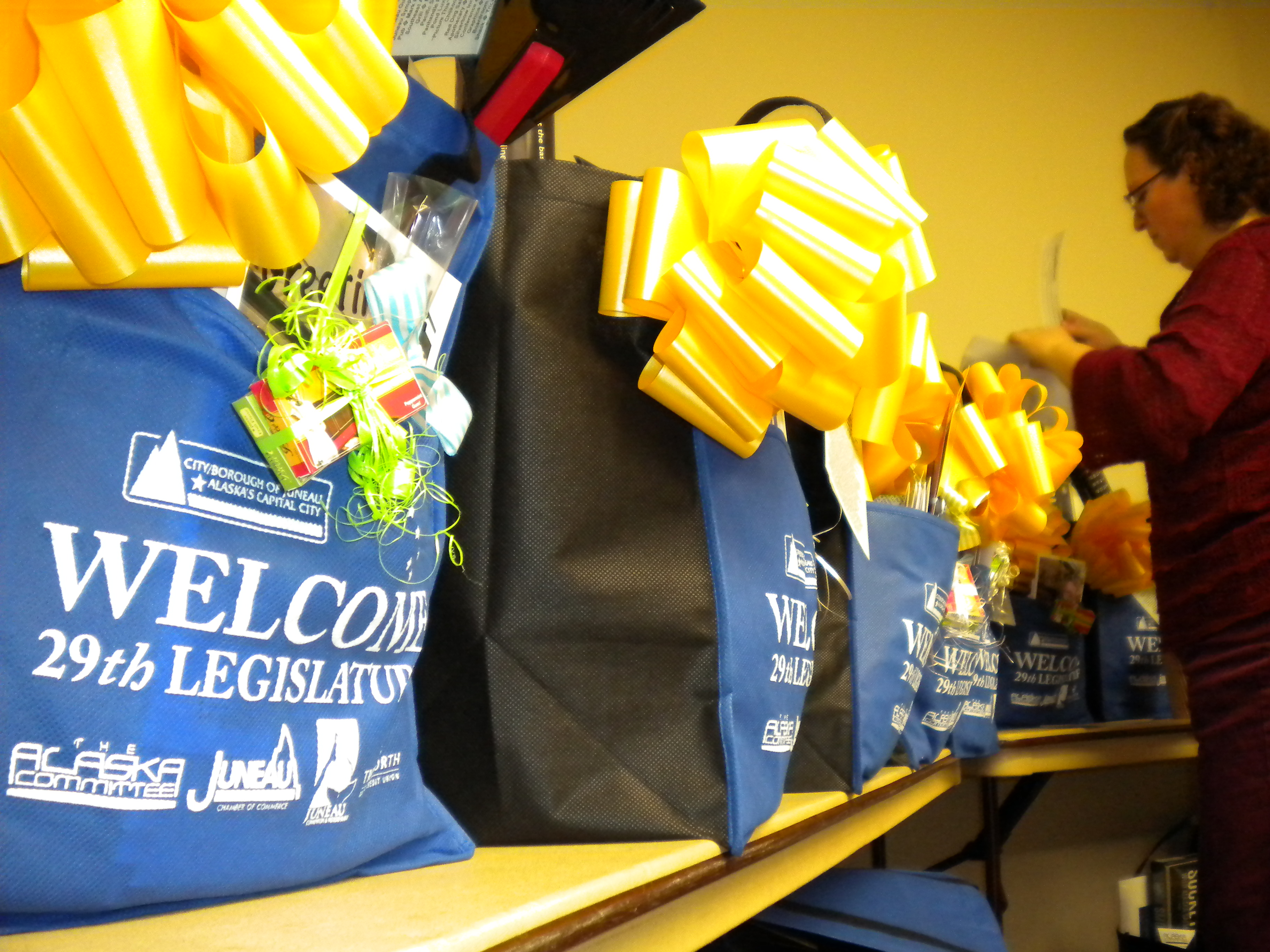 Beth McEwen stuffs gift baskets that will be given out at the 30th annual Legislative Welcome Reception in Centennial hall.