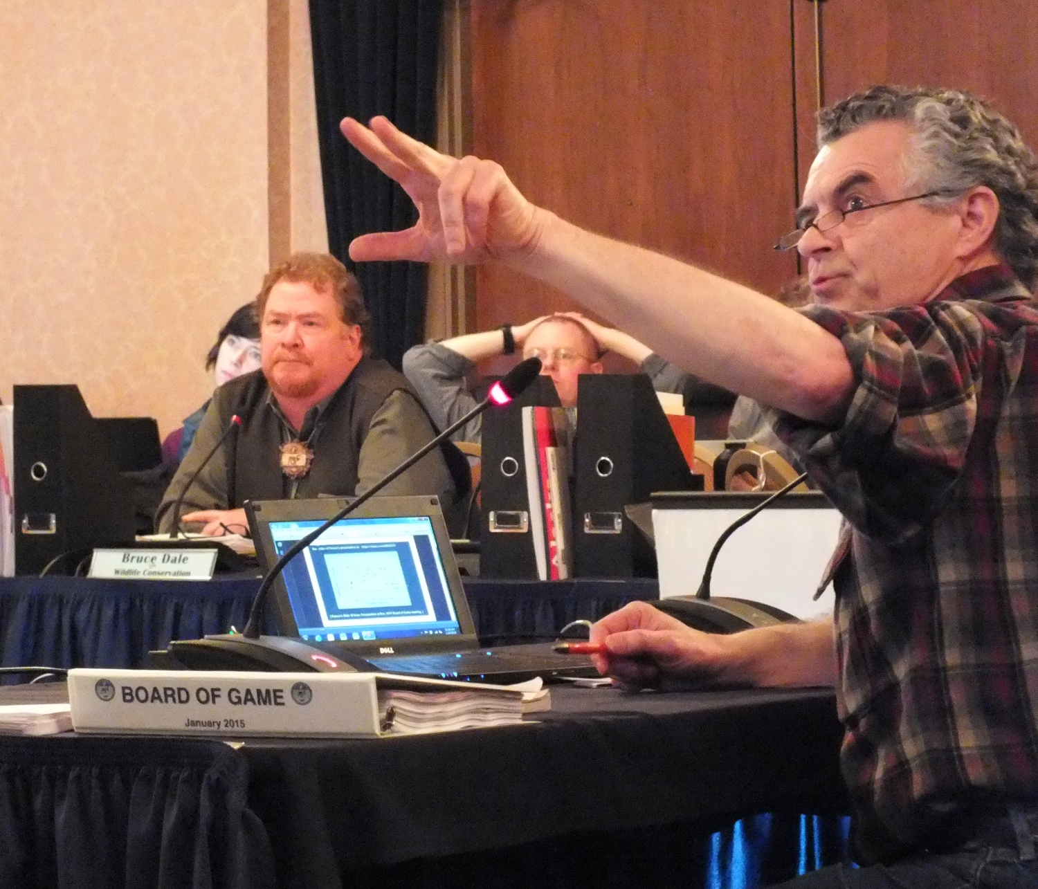 Larry Edwards of Greenpeace (right) points to an overhead projection of a slide while providing testimony on a proposal to limit wolf harvest on Prince of Wales Island as Bruce Dale, acting Director of Division of Wildlife Conservation, listens during the Board of Game's meeting in Juneau on Jan. 9, 2015. (Photo by Matt Miller/KTOO)
