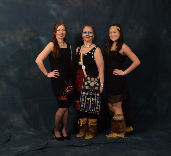 """Rhonda Butler, Ann Chilton and Nancy Barnes are all part of the Yees Ku Oo dance group, which escorted Gov. Bill Walker and Lt. Gov. Byron Mallott into the gala. Butler's dress, which she made, is adorned with her clan crest - double fin killer whale. Chilton wore a traditional regalia octopus bag and a dress made by Butler. Nancy wore her aunt's moccasins and a headband bought at AFN. All three are wearing """"Chilton bling,"""" jewelry made by Chilton brothers Gene, Brian and Doug. (Photo by Skip Gray/KTOO)"""