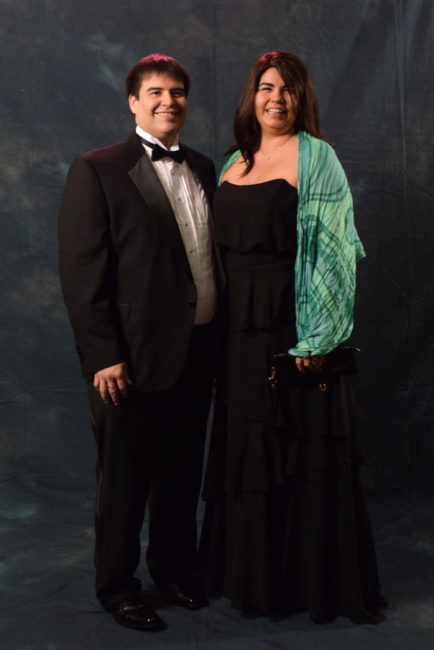 """Ken Southerland and Katie Pittman.  Pittman spent Saturday afternoon shopping and decided on an Alfred Angelo dress from Formals Express. The scarf is from Jineit. Southerland, in a Stafford tux, said, """"It feels good once in a while to get dressed up and be adults.""""  (Photo by Skip Gray/KTOO)"""