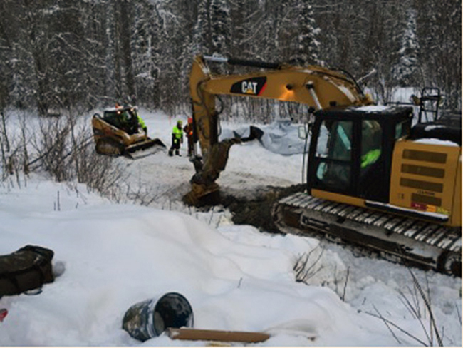 Excavator preparing a test hole on east side of the highway, December 15, 2014 (Photo courtesy Engles-ADEC)