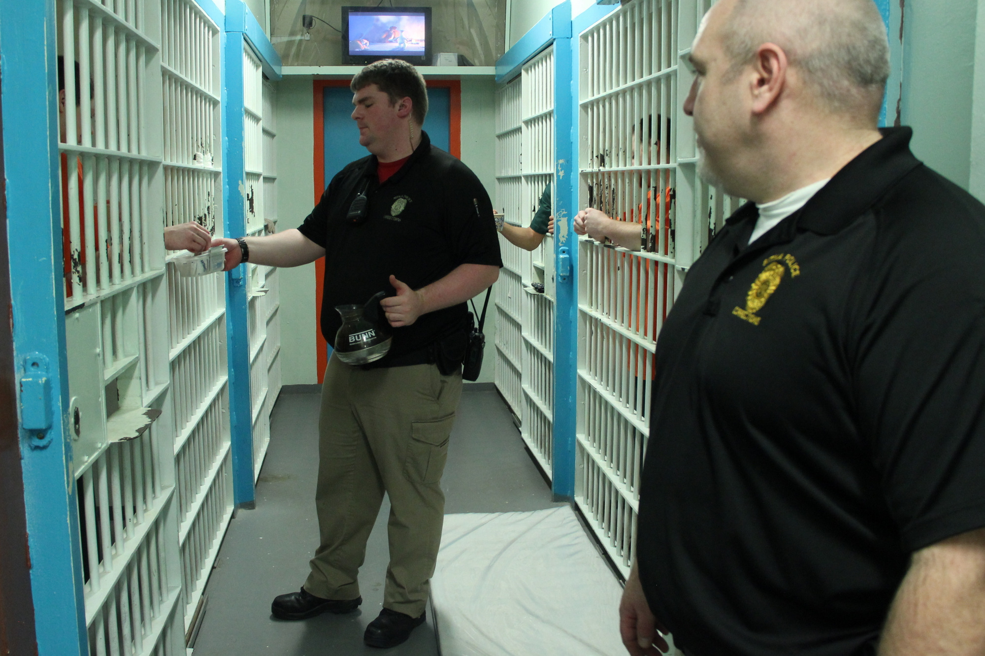Sitka Police Officer Noah Shepard serves coffee to inmates in Sitka's jail, while supervisor Dave Nelson looks on. (KCAW photo/Rachel Waldholz)