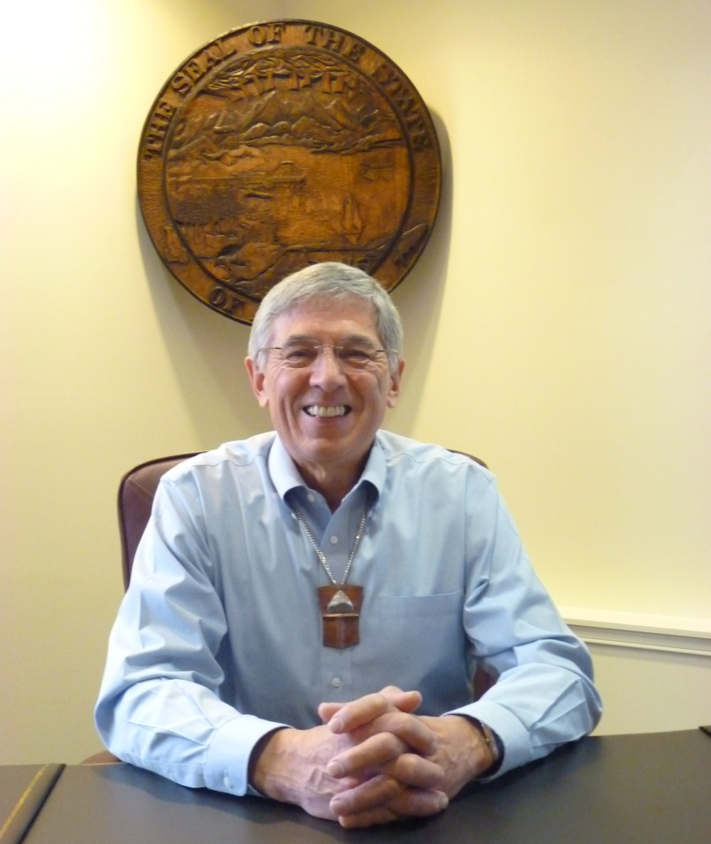 Lt. Gov. Byron Mallott sits at his desk, beneath the state seal Feb. 26. mallott heads up a new administration transboundary mines working group. (Ed Schoenfeld, CoastAlaska News)