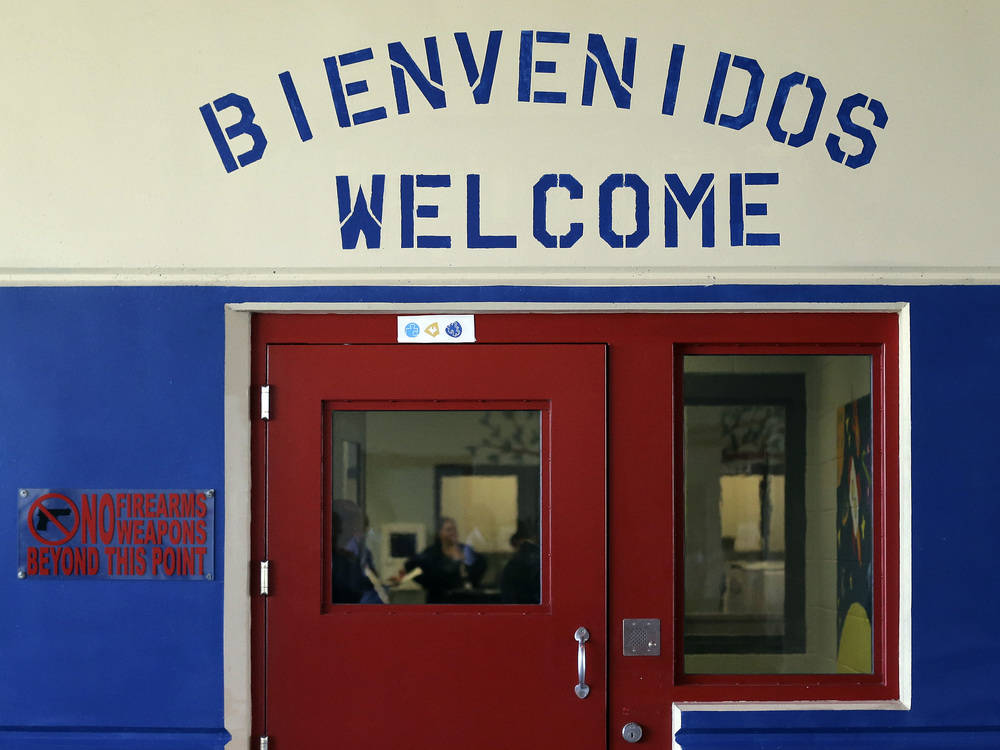 A sign in Spanish and English above the entrance to a secured entrance area at the Karnes County Residential Center in Karnes City, Texas. Eric Gay/AP