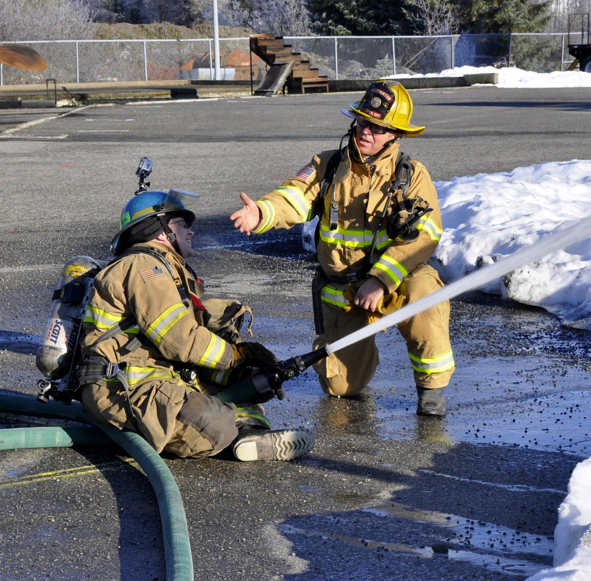 "KTOO reporter Matt Miller learns how to operate a fire hose from his ""shadow"" firefighter Erik Goldsberry at Hagevig Fire Training Center in Jan. 2014. (File photo by Annie Bartholomew/KTOO)"