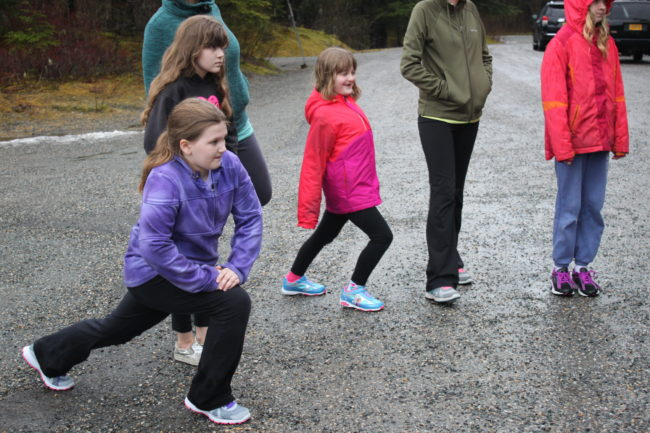 Fifth grader Dani Witt (left) stretches before running. This is her third year doing Girls on the Run. (Photo by Lisa Phu/KTOO)