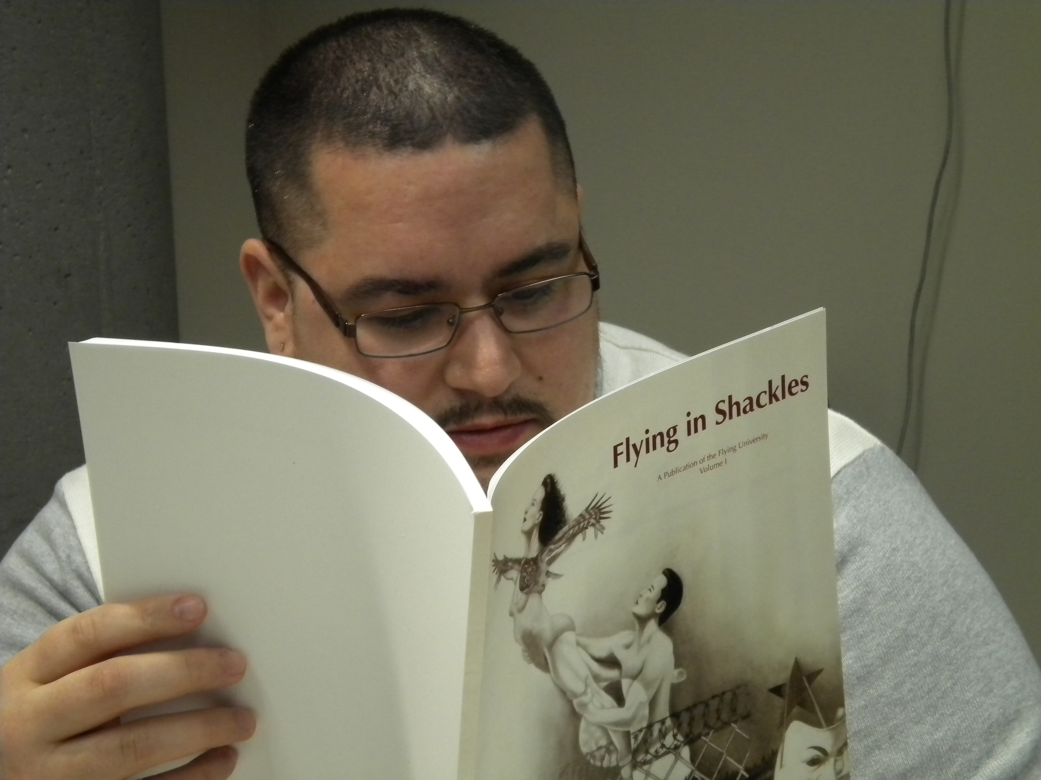 UAS student Marcos Galindo reads an issue of the Flying University literary journal. Galindo is one of the 15 former and current inmates of Lemon Creek Correctional Center to write contributions to the journal. (Photo by Kevin Reagan/ KTOO)