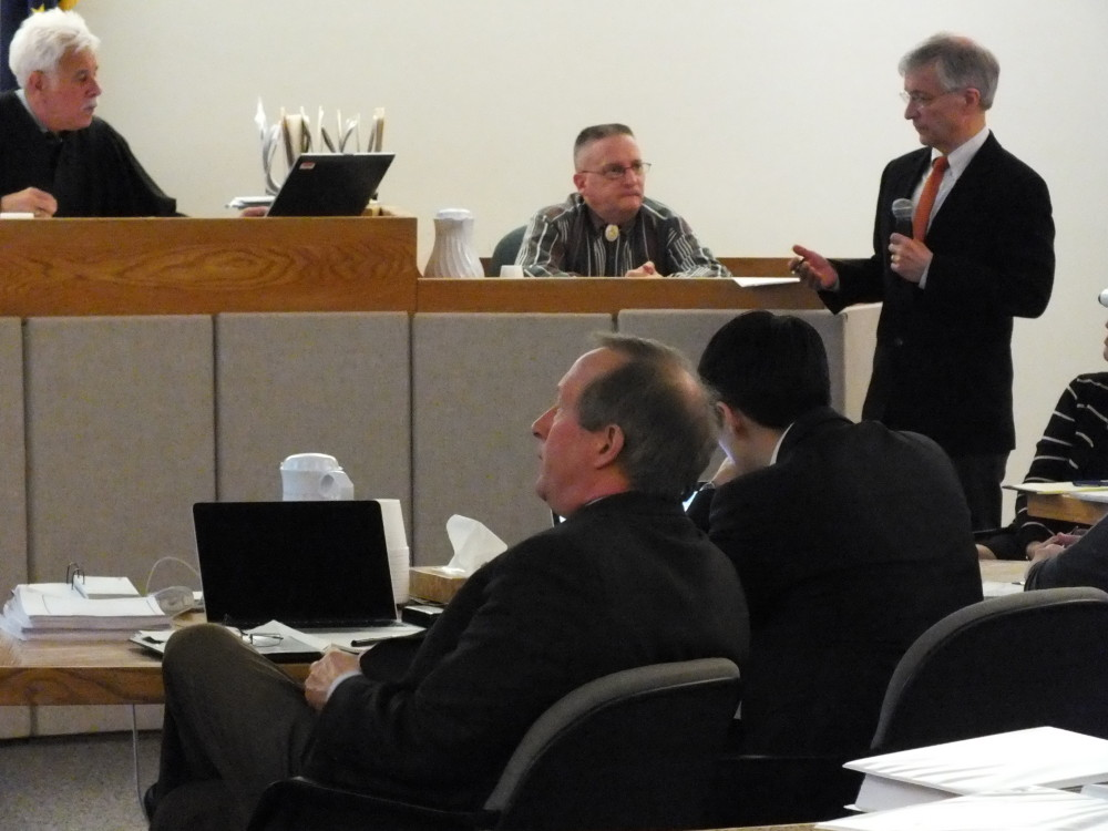Hoonah attorney Frank Koziol questions former Hoonah police chief John Millan. Superior Court Judge Louis Menendez (top left) and Haley Tokuoka-Yearout's attorneys Mark and Jon Choate (bottom) listen and view an overhead projection seen by the jury. (Photo by Matt Miller/KTOO)