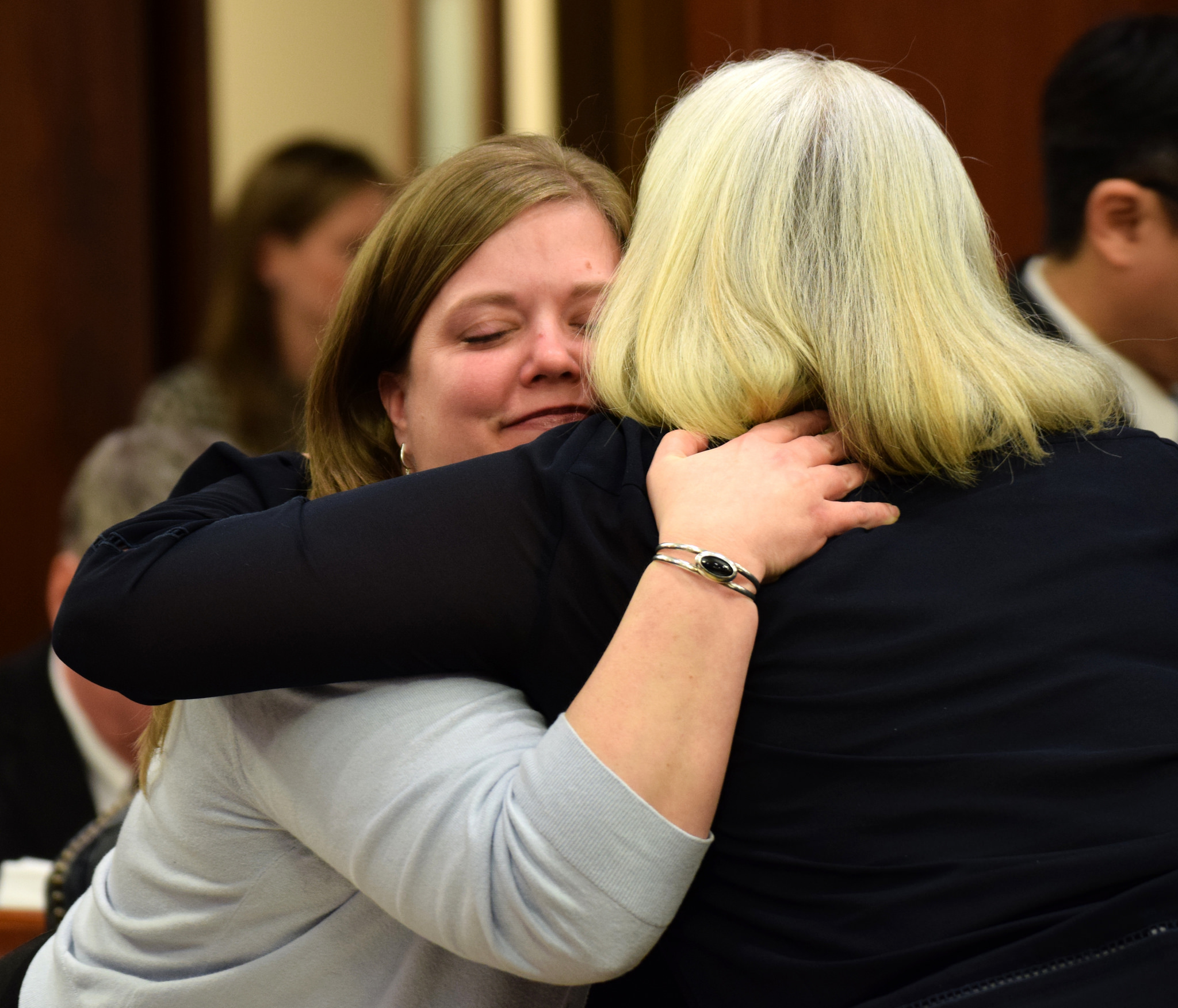 """Rep. Geran Tarr, D-Anchorage, gets a congratulatory hug from Rep. Cathy Muñoz, R-Juneau, after the house passes House Bill 44. Tarr first brought """"Erin's Law"""" to the legislature last year. (Photo by Skip Gray/360 North)"""