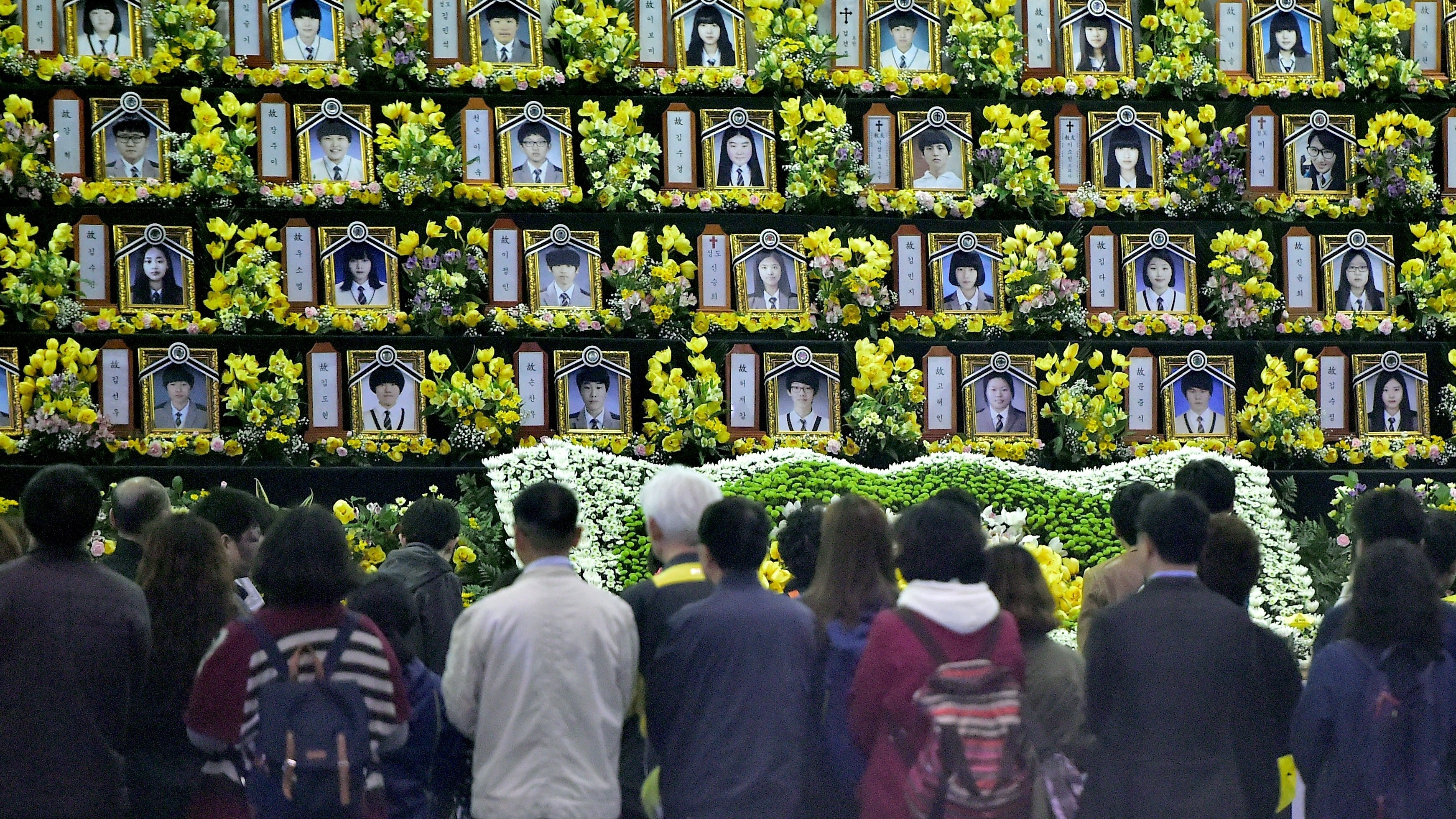 People pay tribute at a group memorial altar for victims of the sunken South Korean ferry Sewol at a remembrance hall in Ansan on Thursday. (Photo by Jung Yeon-Je/AFP/Getty Images)