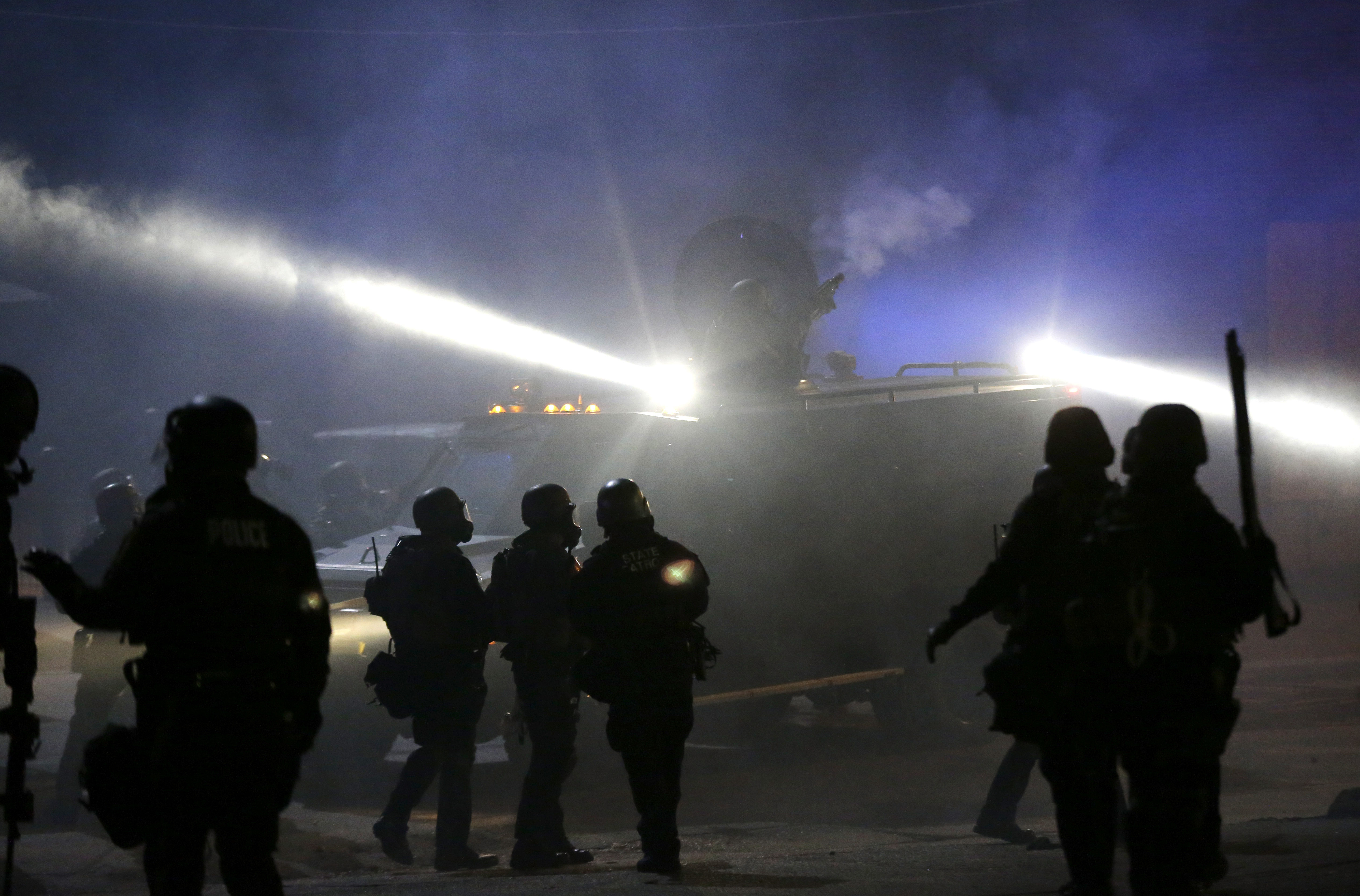 Police in riot gear stand around an armored vehicle as smoke fills the streets of Ferguson, Mo., in November 2014. Charlie Riedel/AP