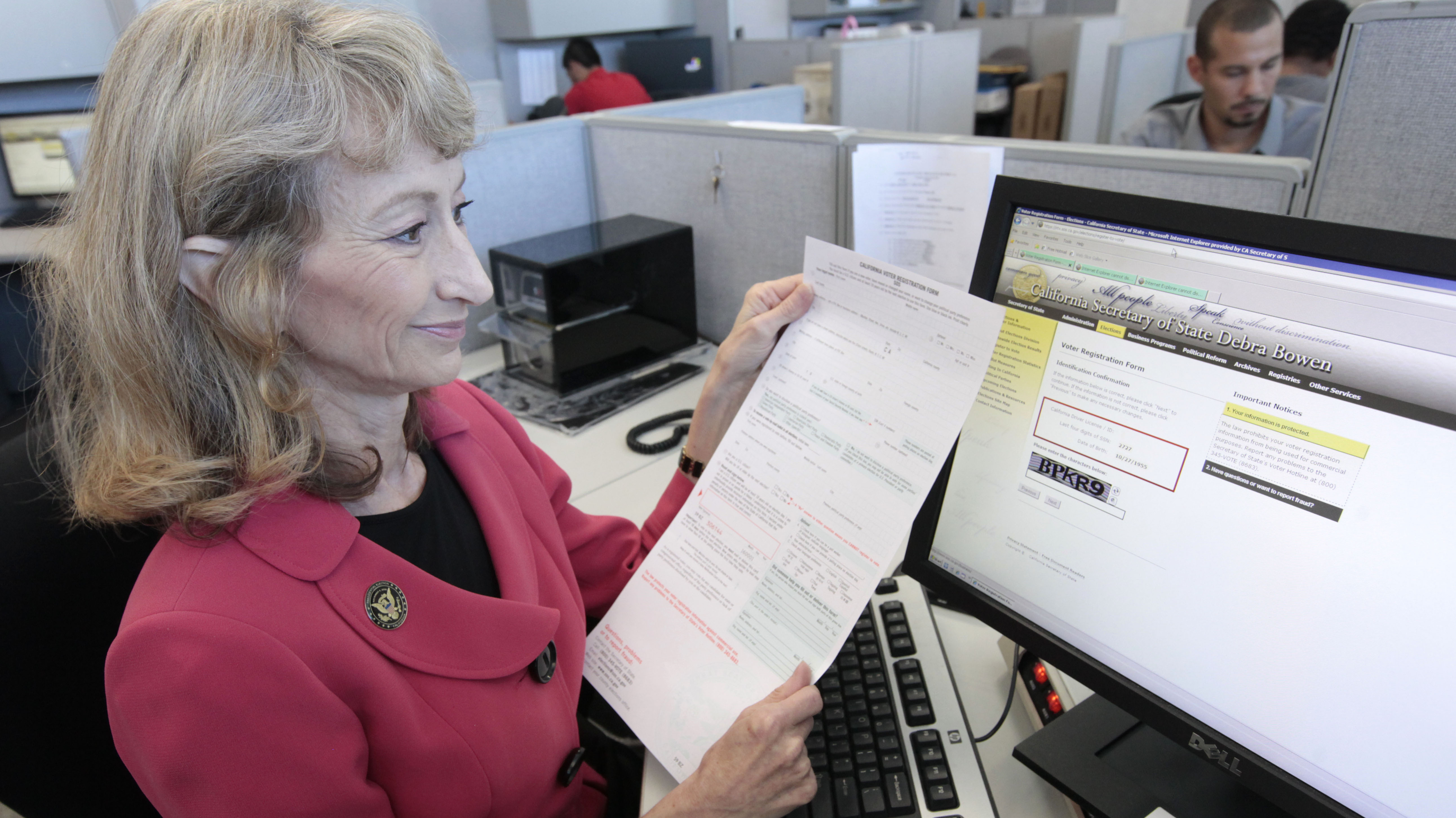 Debra Bowen, then California secretary of state, demonstrates the state's online voter registration system when it was launched in 2012. Voters can also still register using a paper form. Rich Pedroncelli/AP