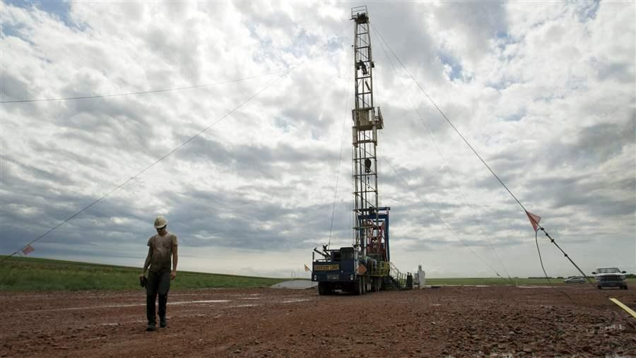 An oil worker walks away from a derrick near Williston, North Dakota. Lower oil prices are causing financial worries in some states that rely heavily on oil taxes. (AP)