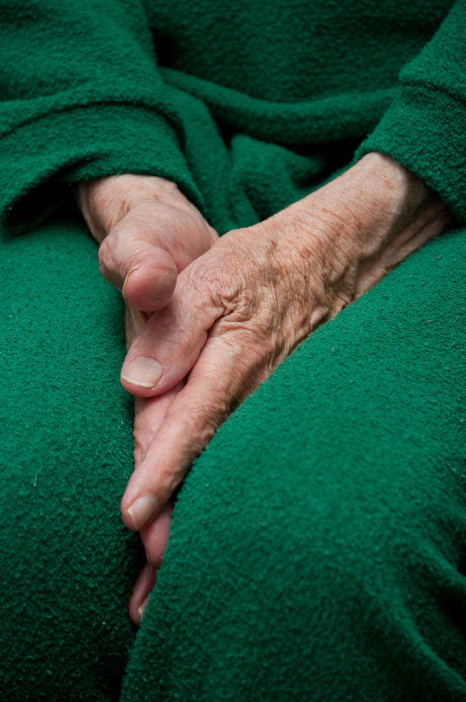 Old woman's hands with deep wrinkles and protruding veins tucked between her legs. She is wearing a bright green sports suit. (Creative Commons photo by Horia Varlan)