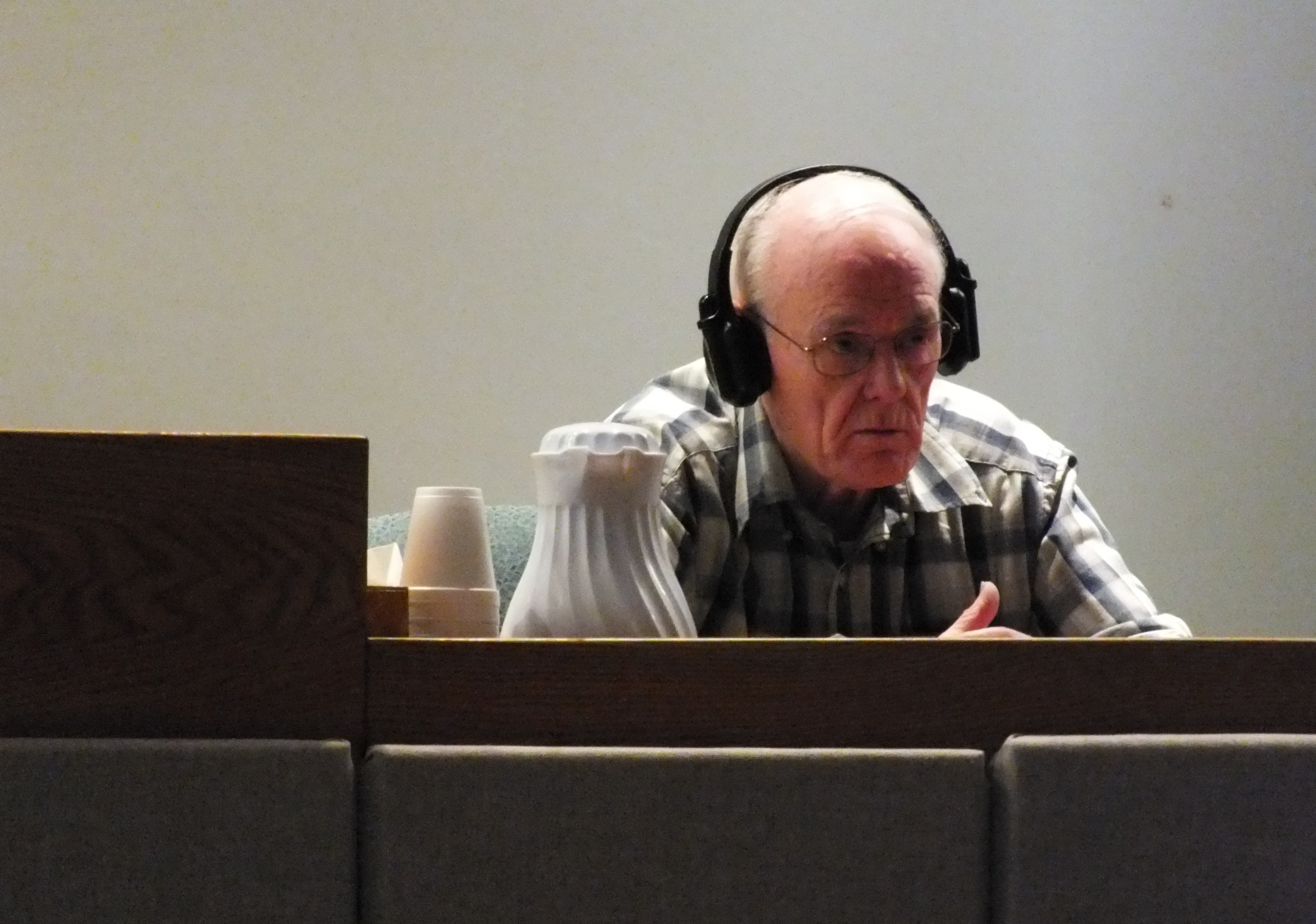 Rayco Sales owner Ray Coxe wears a set of hearing-assist headphones as he listens to a question  in Juneau Superior Court during his civil trial in June. (Photo by Matt Miller)