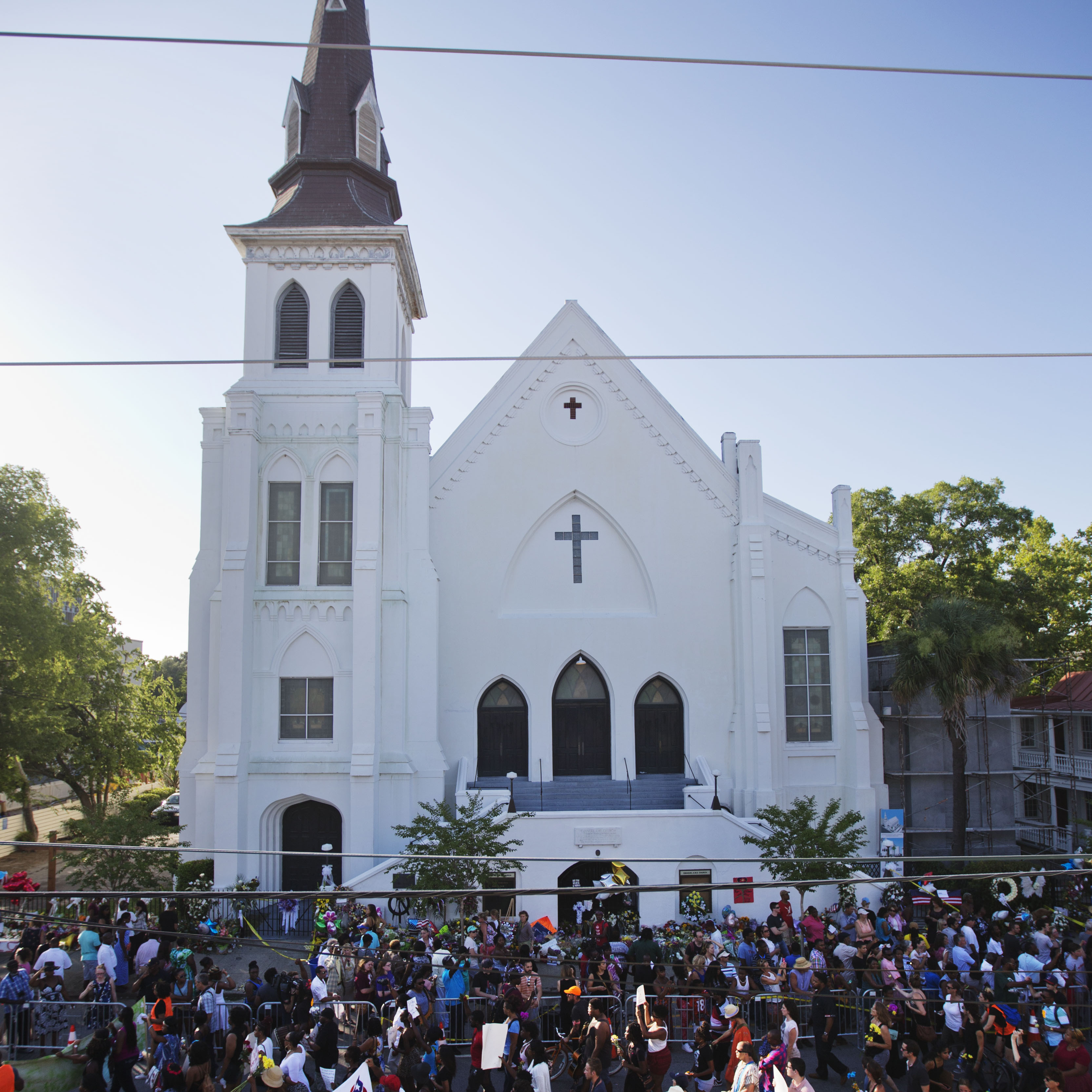 A remembrance march in memory of the Emanuel AME Church shooting victims passes a sidewalk memorial in front of the church on Saturday. The church today will hold its first Sunday service since Wednesday's shooting. David Goldman/AP