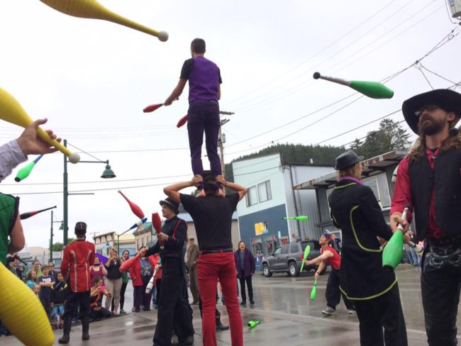 """New Old Time Chautauqua jugglers in a rainy teaser show in Wrangell on June 26, 2015. (Photo by Zachary """"Skip"""" Waddell/New Old Time Chautauqua)"""