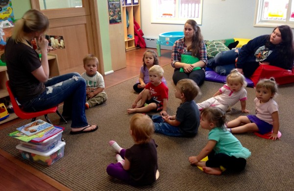 Teacher Theressa Phillips reads to the toddler class with Assistant teacher, Brina Compton and teen worker, Kallie Caples looking on. (Photo by Angela Denning/KFSK)