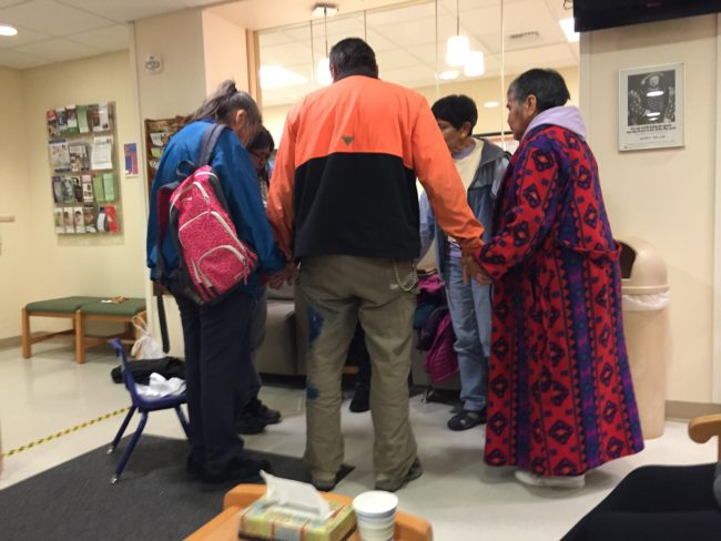 Family and friends of plane crash survivor Ernestine Hanlon-Abel of Hoonah pray together at Bartlett Regional Hospital Friday night. (Photo by Lisa Phu/KTOO)