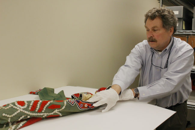 Chuck Smythe unrolls the tunic from storage. (Photo by Elizabeth Jenkins/KTOO)