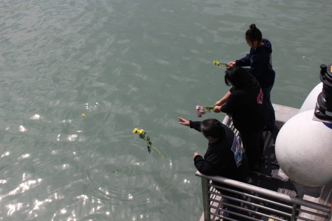Family members aboard the Douglas Indian Association chartered cruise threw flowers into the water to honor deceased relatives. (Photo by Elizabeth Jenkins/KTOO)