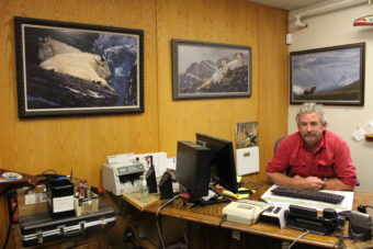 Mitch Falk's office walls are adorned with pictures of goats and wildlife. He enjoys goat hunting when he gets the chance. (Photo by Elizabeth Jenkins/KTOO)