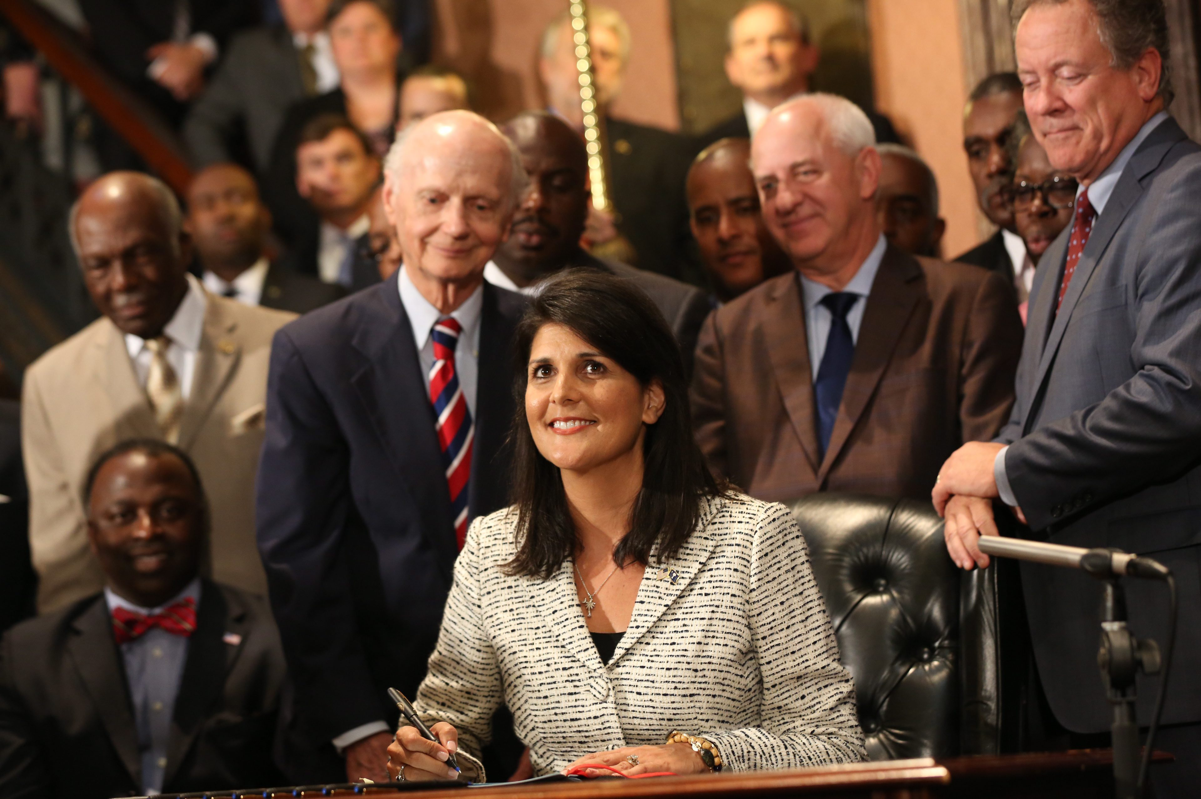With her predecessors in the governor's office and others looking on, Gov. Nikki Haley signs into law a bill that removes the Confederate flag from the State House in Columbia.