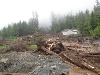 A new home under construction on Sitka's Kramer Avenue was obliterated in the slide, Aug. 18, 2015. A neighboring home is unscathed. (Photo by Joel Curtis/National Weather Service)