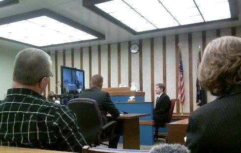 David Mason (far left) and his attorney Marcelle McDannel (far right) watch as state prosecutor Ben Hofmeister (second from right) question forensic scientist Jennifer Foster via video conferencing. Also pictured is officer Charles Johnson, second to the left. (Photo by Madelyn Beck, KRBD)